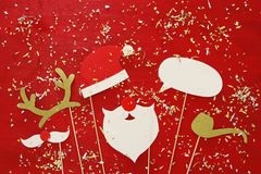 Christmas concept top view image. Santa claus beard and hat on red wooden background. Royalty Free Stock Photo