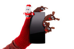 Christmas concept toy Santa Claus and reindeer with a gift in hand smartphone Stock Photo