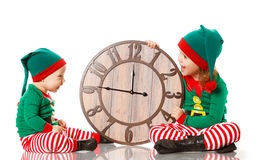 Christmas concept. Two little elf helper of Santa with clock iso royalty free stock photo