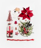 Christmas concept. Various holiday objects: gift, Christmas tree, table place setting with cutlery and decorations, fir branches. Pine cones and poinsettia on stock photo