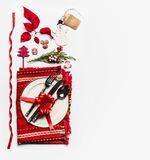 Christmas concept. Various holiday objects: table place setting with cutlery and decorations, fir branches, snowman, cones, tags. Ribbon and poinsettia on royalty free stock photography