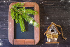 Christmas concept. Vintage chalk board, spruce branches and birdhouse Royalty Free Stock Image