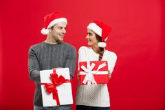 Christmas Concept - Young attractive couple giving gifts to each other celebrating in Christmas day royalty free stock images