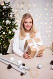Christmas concept - young beautiful blond woman sitting with gif stock image