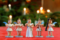 Christmas Concert with Five Musician Angels. Closeup of five decoration angels making music in front of Christmas Tree lights background stock photo