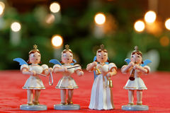 Christmas Concert with Four Angels. Four decoration angels making music in front of Bokeh Christmassy lights royalty free stock images