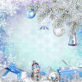 Christmas congratulatory background with pine branches, gifts and Christmas decorations. Blue snowy background with pine branches, Christmas decorations and Royalty Free Stock Photo