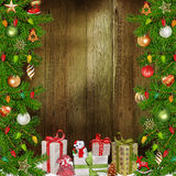 Christmas congratulatory background with pine branches, gifts, Christmas decorations. Wooden background with pine branches, Christmas decorations, gifts Royalty Free Stock Images