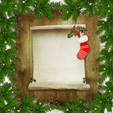 Christmas congratulatory background with pine branches, a roll of paper for text and Christmas socks on a wooden background Royalty Free Stock Images
