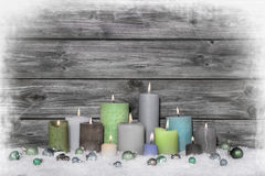 Christmas congratulatory card with many candles on wooden grey s. Christmas congratulatory card with many colored candles on wooden grey shabby chic background Stock Photography