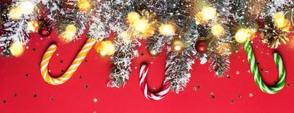Christmas coniferous border with shining lights and candy canes on red background.  royalty free stock images