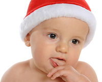 Christmas Contemplation. An adorable baby in Santa's hat spacing out as he contemplates the season.  Isolated on white Stock Photos