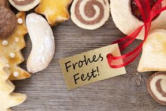 Christmas cookie background with Frohes Fest. Christmas cookie background on wood with golden label with the german words frohes fest which means merry christmas Royalty Free Stock Photos