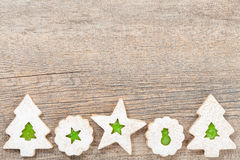 Christmas Cookie Border. Overhead view of green jam filled Christmas Linzer cookies decorated with icing sugar and arranged as a border on a wooden background royalty free stock images
