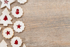 Christmas Cookie Border. Overhead view of jam filled Christmas Linzer cookies decorated with icing sugar and arranged as a border on a wooden background. Copy royalty free stock photos