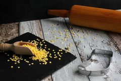 Christmas cookie cutter boots and yellow sugar stars with rolling pin on wooden table stock photo