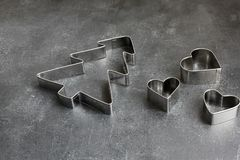Christmas cookie cutter christmas tree and hearts on dark board stock photo