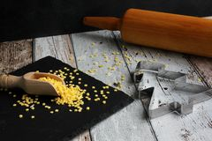 Christmas cookie cutter christmas tree and yellow sugar stars with rolling pin on wooden table stock photos