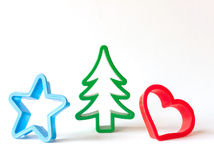 Christmas cookie cutters. Pastry cutters for Christmas cookies, in different shapes and colors, against white background stock photos