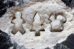 Christmas Cookie Cutters on Flour and Black Background Royalty Free Stock Image
