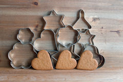 Christmas cookie cutters and gingerbread cookies. On wooden background Stock Image