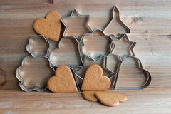 Christmas cookie cutters and gingerbread cookies. On wooden background Royalty Free Stock Photo