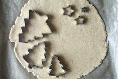 Christmas cookie cutters on the raw dough on the parchment top view Stock Photos
