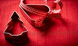 Christmas cookie cutters on red background. Closeup of two christmas cookie cutters on red background Royalty Free Stock Photography