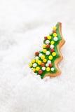 Christmas cookie, glazed christmas tree shape on a snow Royalty Free Stock Photo