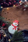 Christmas cookie Snowman and festive decor. Place for text at wooden background royalty free stock image