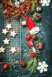 Christmas cookie and winter decoration with Santa hat and wreath on rustic wooden background Royalty Free Stock Photos