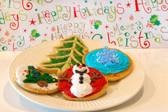 Christmas Cookies. A plate of decorated holiday cookies against a cheerful happy holidays background Stock Photo