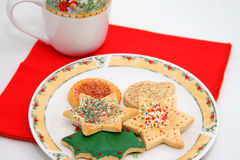 Christmas cookies. Christmas cookines on a snowman plate with red napkin and a cup Royalty Free Stock Photo