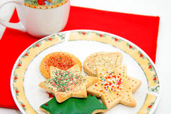 Christmas cookies. Christmas cookines on a snowman plate with red napkin and a cup Royalty Free Stock Image