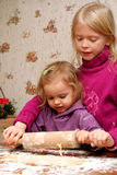Christmas cookies. Children rolling out dough for christmas cookies Royalty Free Stock Photography
