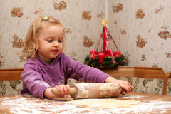 Christmas cookies. Children rolling out dough for christmas cookies Stock Images