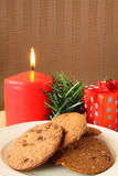 Christmas cookies. Serving on white plate with red candle at background stock photos