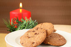 Christmas cookies. Serving on white plate with red candle at background royalty free stock photography