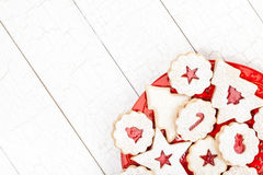 Christmas Cookies. Beautiful assorted Christmas cookies arranged on a red plate over a white wooden background royalty free stock images