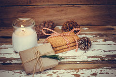 Christmas cookies with burning candle, giftbox and pine cones Royalty Free Stock Images