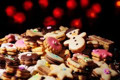 Christmas cookies and cakes in warm lights. Lots of Christmas cookies and cakes against the background of blurred warm red lights Royalty Free Stock Photo