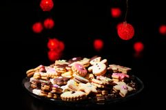 Christmas cookies and cakes in warm lights. Lots of Christmas cookies and cakes against the background of blurred warm red lights Stock Photo