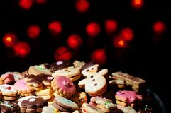 Christmas cookies and cakes in warm lights. Lots of Christmas cookies and cakes against the background of blurred warm red lights Stock Image