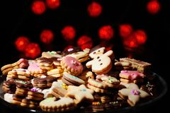 Christmas cookies and cakes in warm lights. Lots of Christmas cookies and cakes against the background of blurred warm red lights Stock Images