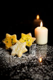 Christmas cookies and a candle on a black background with copysp Royalty Free Stock Photography