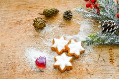 Christmas cookies. Pinecones,heart and   red ribbon and sugar  on vintage wood background - dark moody image of decorative food, simple composition Royalty Free Stock Image