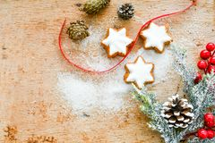 Christmas cookies. Pinecones and red ribbon and sugar on vintage wood background - dark moody image of decorative food, simple composition stock photos