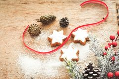 Christmas cookies. Pinecones and  red ribbon and sugar  on vintage wood background - dark moody image of decorative food, simple composition Royalty Free Stock Photography