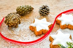 Christmas cookies. Pinecones and  red ribbon and sugar  on vintage wood background - dark moody image of decorative food, simple composition Royalty Free Stock Photos