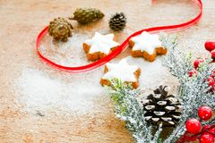 Christmas cookies. Pinecones and  red ribbon and sugar  on vintage wood background - dark moody image of decorative food, simple composition Royalty Free Stock Image